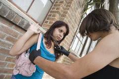 Female Robber Scaring A Woman With Knife. Female robber with a knife scaring young woman Stock Photography