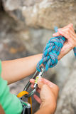 Female rock climber adjusting her harness. By the rock face Royalty Free Stock Images