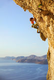 Female rock climber on challenging route on cliff Stock Photography