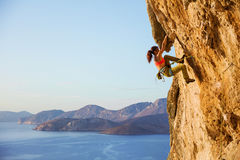 Female rock climber on challenging route on cliff, view of coast. Below stock photography