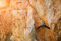 Female rock climber. Climbs on a rocky wall.  woman standing in an uncomfortable position with legs wide apart, almost splits Stock Image