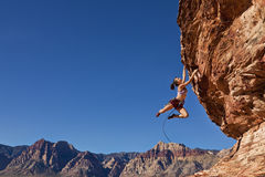 Female rock climber clinging to a cliff. Royalty Free Stock Image
