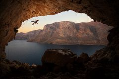 Female rock climber falling of cliff in big cave Stock Images