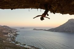 Female rock climber hanging upside down on challenging route in cave at sunset. Resting before keeping on her attempt stock photos