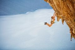 Female rock climber jumping on handholds on challenging route on cliff. With view of sea and coast below royalty free stock images