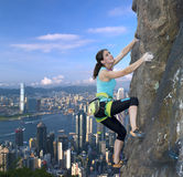 Female rock climber over the city skyline Royalty Free Stock Image