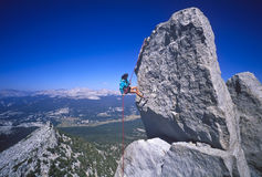 Female rock climber rappelling. Stock Photos