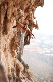 Female rock climber resting while hanging on rope stock image