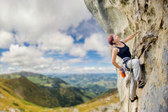 Female rock climber on steep overhanging rock cliff Royalty Free Stock Images