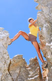 Female rock climber steps between rocks Royalty Free Stock Image