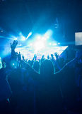 Female At Rock Concert. Anonymous Woman with Arms Up in Crowd of People Looking Towards Brightly LIt Stage Stock Photos