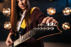 Female rock guitarist in suit tunes the guitar. Stage with lights on background, retro style. Live music performer Royalty Free Stock Images