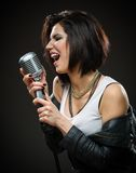 Female rock singer handing microphone Stock Photo