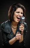 Female rock singer keeping microphone Royalty Free Stock Photography