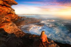 Female on rocks watching the ocean cascade around coastal rocks stock photo