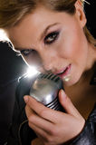 Female rocksinger caressing microphone Royalty Free Stock Photos
