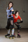 Female Roller Derby Skaters. Pair of tough Caucasian female roller derby skaters Royalty Free Stock Photo