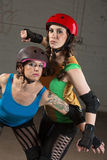 Female Roller Derby Skaters. Pretty roller derby skater with tattoo and partner posing Royalty Free Stock Photo