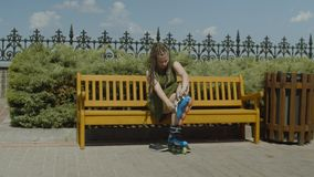 Female roller putting on roller blades on bench. Attractive woman roller sitting on bench and putting roller skates on feet before riding in well-kept public stock video