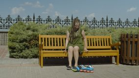 Female roller putting on shoes sitting on bench. Young woman putting on shoes after taking roller skates off sitting on park bench. Active sporty female roller stock video footage