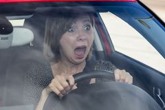 Female rookie new driver young beautiful woman scared and stressed while driving car in fear and shock. Face expression screaming in panic Stock Photos