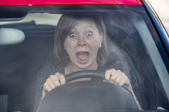 Female rookie new driver young beautiful woman scared and stressed while driving car in fear and shock. Face expression screaming in panic Royalty Free Stock Photography
