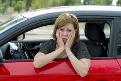 Female rookie new driver young beautiful woman scared and stressed while driving car in fear and shock. Face expression in stress and confusion Royalty Free Stock Images