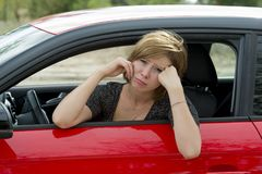 Female rookie new driver young beautiful woman scared and stressed while driving car in fear and shock. Face expression in stress and confusion Stock Photo