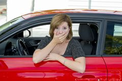 Female rookie new driver young beautiful woman scared and stressed while driving car in fear and shock. Face expression in stress and confusion after crashing Royalty Free Stock Image