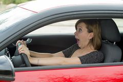 Female rookie new driver young beautiful woman scared and stressed while driving car in fear and shock Stock Photos