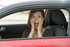 Female rookie new driver young beautiful woman scared and stressed while driving car in fear and shock. Face expression screaming in panic royalty free stock photo