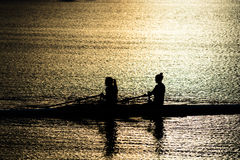 Female Rowers on Sunset Lake Royalty Free Stock Image