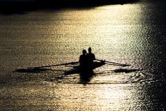 Female Rowers on Sunset Lake Royalty Free Stock Photography