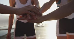 Female rowing team training on a river. Front view mid section of a team of four young adult Caucasian female rowers stacking hands together and raising them in stock video