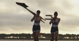 Female rowing team training on a river. Front view of two young adult Caucasian female rowers taliking and carrying oars before training on a river stock video