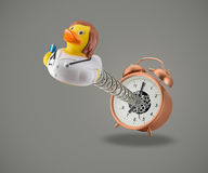 Female Rubber duck doctor coming out of alarm clock Stock Images
