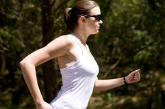 Female runner. Young active female running outside with green trees  background Stock Photo
