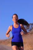 Female Runner. Beautiful asian woman running highlighted against bright, blue sky Stock Photography