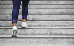 Female runner athlete doing a stairs climbing. Running woman doing run up steps on staircase in urban city. Doing cardio sport