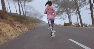 Female runner athlete running on country road stock footage
