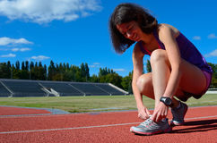 Female runner athlete tying laces of running shoes for training and jogging on stadium track, sport and fitness Royalty Free Stock Images