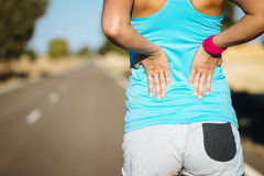 Female runner back pain. Female runner athlete back injury and pain. Woman suffering from painful lumbago or kidney illness while running in rural road Stock Images