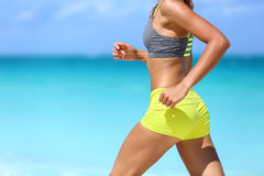 Female runner on beach with sports bra and shorts Stock Images