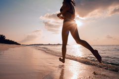 Female Runner on the Beach at Sunset silhouette in air farther Stock Photography
