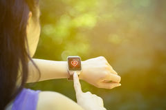 Female runner checking heart rate on smart watch outdoors. Young female athlete looking at heart rate app and checking beats per minute on her smart watch in the stock images