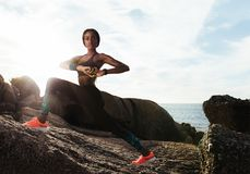Female runner doing stretches at rocky beach Royalty Free Stock Photography