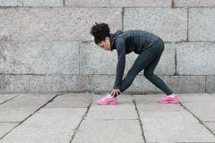 Female runner doing warm up exercise before training. On city street royalty free stock images