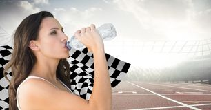 Female runner drinking on track against flares and checkered flag. Digital composite of Female runner drinking on track against flares and checkered flag Stock Images