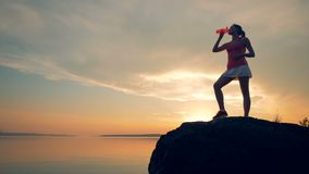 Female runner drinks water, slow motion. A woman stands on a rock near water, drinking on a sunset background. A woman stands on a rock near water, drinking on stock video footage