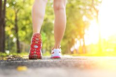 Female runner feet running closeup on shoe. Closeup of athlete female feet in running shoes jogging on the road early in the morning. Healthy lifestyle stock photos
